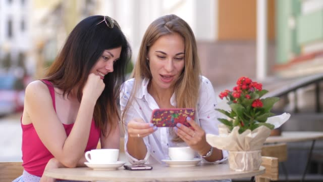 Two beautiful young women sit at the table in cafe and look in the phone. 4k. slow motion