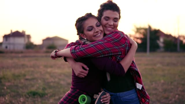 Two best friends hugging each other and looking in the camera smiling. Happy young woman cuddle and hug showing love and affection. Slowmotion shot. Lens flare - video