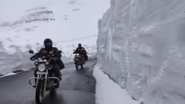 Two bikers on Royal Enfield crossing the famous Baralacha pass in Himachal Pradesh, India. Two bikers on Royal Enfield crossing the famous Baralacha pass in Himachal Pradesh, India. royalty stock videos & royalty-free footage