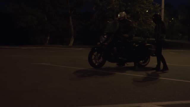 vídeos de stock e filmes b-roll de two bikers sit on their motorcycle and riding away on the night road - helmet motorbike
