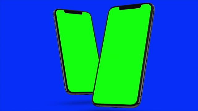 Video Two Black smartphone turns on on blue background. Easy customizable green screen. Computer generated image.