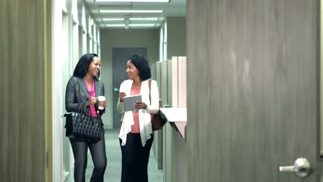Two black women conversing, walking down office hallway Two multi-ethnic businesswomen carrying shoulder bags, walking down an office corridor, talking and looking at a digital tablet. The woman with curly hair is mixed race African-American and Native American. cube stock videos & royalty-free footage