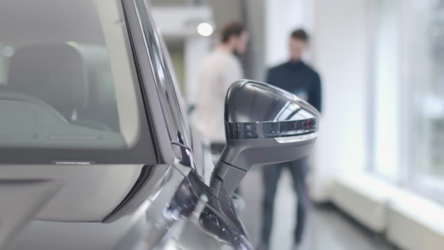 Two blurred Caucasian men in casual clothes talking at the background. Close-up of black side view mirror at the foreground. Car dealership, car business. Cinema 4k footage ProRes HQ. Two blurred Caucasian men in casual clothes talking at the background. Close-up of black side view mirror at the foreground. Car dealership, car business. Cinema 4k footage ProRes HQ. car salesperson stock videos & royalty-free footage