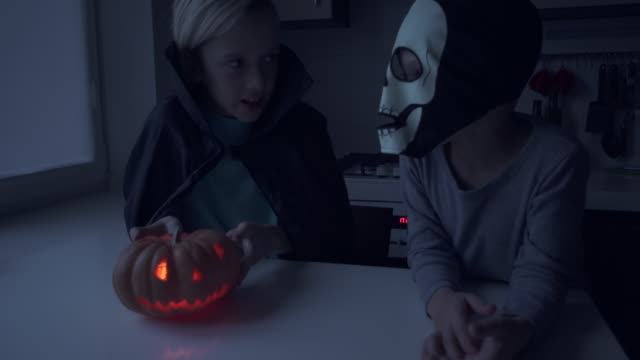 Two boy in scary halloween costumes playing with jack-o-lantern video