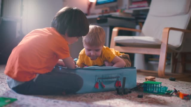 Two boys are playing with a constructor box.