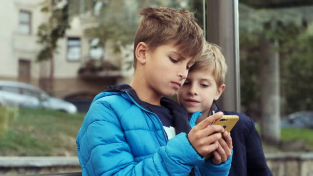 Two Boys Are Sitting At The Bus Stop.