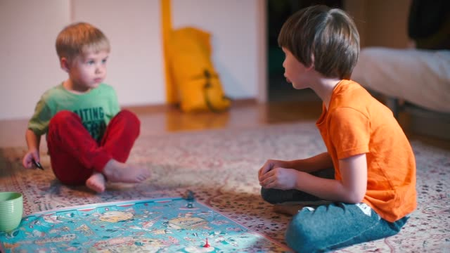 Two boys are sitting on the floor and playing a board game.