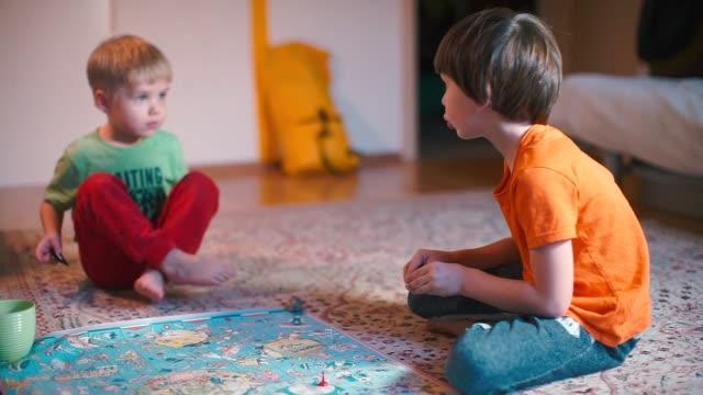 vídeos de stock, filmes e b-roll de dois meninos estão sentados no chão e jogando um jogo de tabuleiro. - game