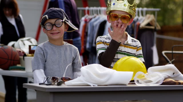 Two boys at garage sale with funny hats and glasses video