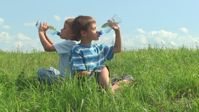 due maschi bere acqua calda giornata d'estate - acqua potabile video stock e b–roll