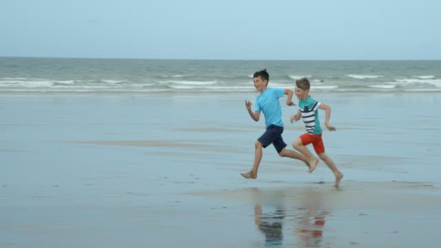 Zwei Jungs, die Spaß im Rennen am Strand in Zeitlupe. – Video