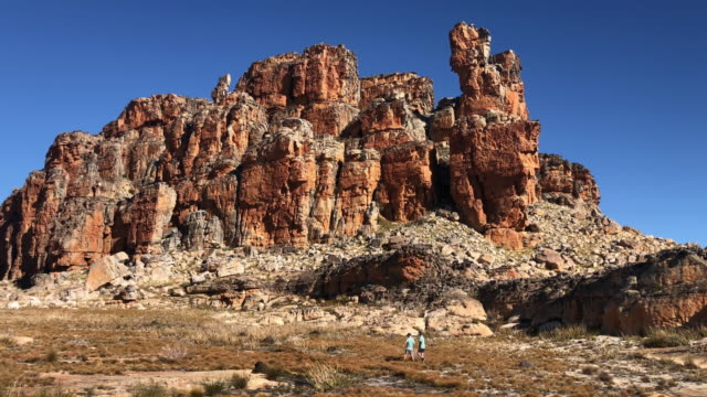 Two Boys Hiking past a spectacular rock formation