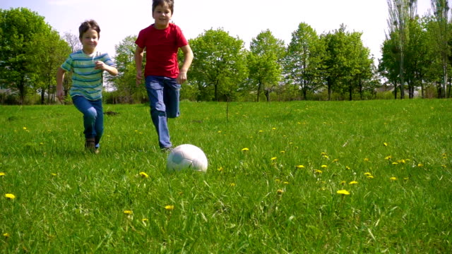 Two boys hit the ball on green meadow, slow motion