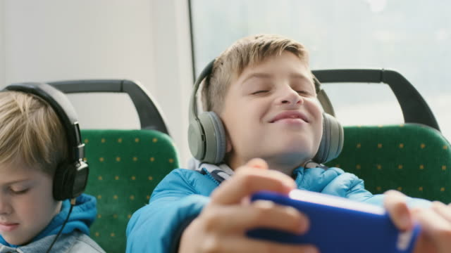 Two Boys In The Passenger Seat On The Bus Playing Smartphones.