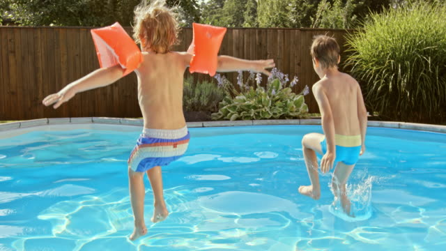 SLO MO DS Two boys jumping into the pool in sunshine