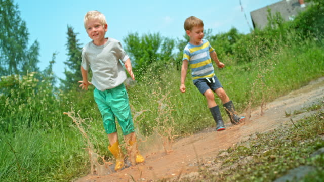 stockvideo's en b-roll-footage met slo mo twee jongens springen op en neer in een modderige plas in zon - t shirt