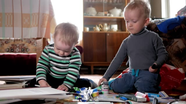 Two boys play at home with stationery. Cute brothers spend interesting time Two boys play at home with stationery. Cute brothers spend interesting time. playroom stock videos & royalty-free footage