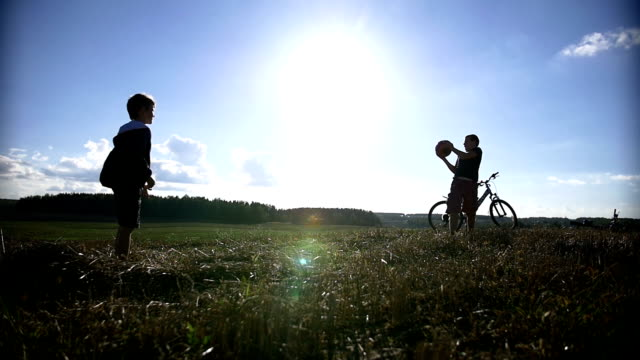 two boys playing with a ball on top of the field, throw up the ball video