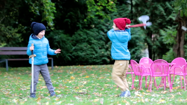 Two boys, playing with swords in the park, autumn time video