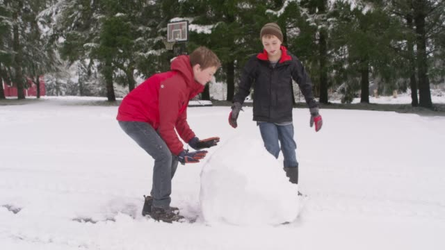 two boys rolling a snow ball in winter - rotolare video stock e b–roll