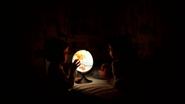 two boys sitting in bed at night rotating the globe and dreams of traveling. - curiosità video stock e b–roll