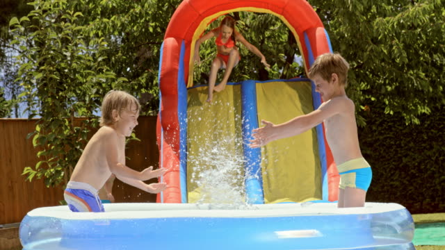 SLO MO Two boys splashing water at each other in an inflatable pool video