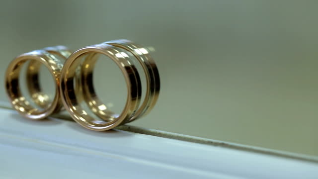 Two bridal golden rings stand on white windowsill video