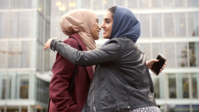 Two British Muslim Women Friends Meeting Outside Office video