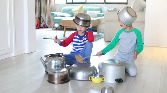 two brother playing on floor with pots and pans - kitchen situations video stock e b–roll