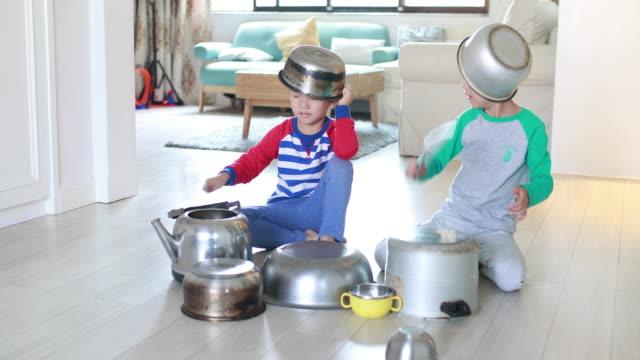 två bror spelar på golvet med kastruller och stekpannor - trumset bildbanksvideor och videomaterial från bakom kulisserna