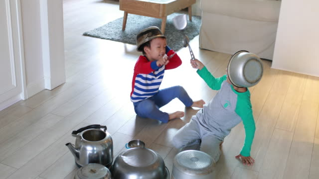 two brother playing on floor with pots and pans - brother stock videos and b-roll footage