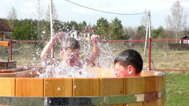 水しぶきを楽しんで 2 人の兄弟 - 兄弟点の映像素材/bロール