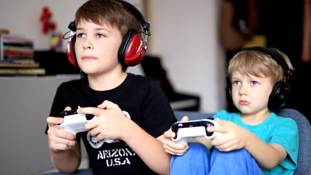 vídeos de stock e filmes b-roll de two brothers playing on games console - tv e familia e ecrã