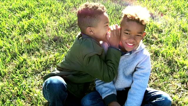 笑いながらお互いの耳にささやく二人の兄弟 ビデオ