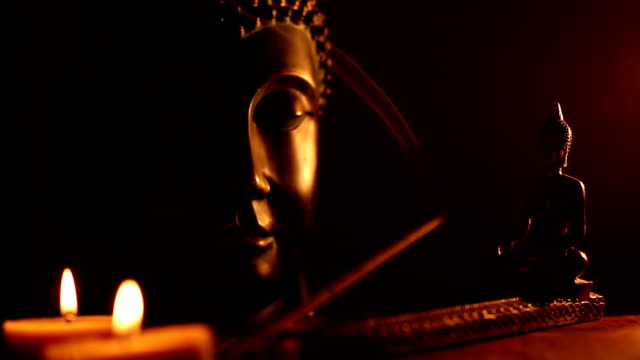 two Buddha statue with candles and smoke of incense video