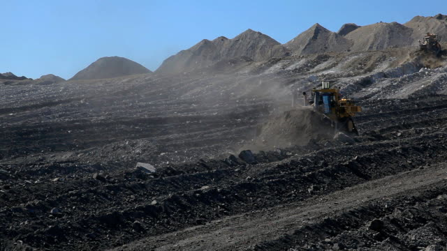 Two bulldozers moving earth at a coal mine video