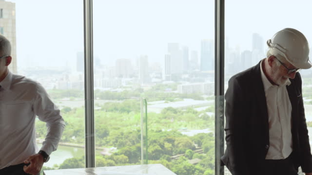 two business man shaking hands each other over window on cityscape background . deal of real estate agent with customer