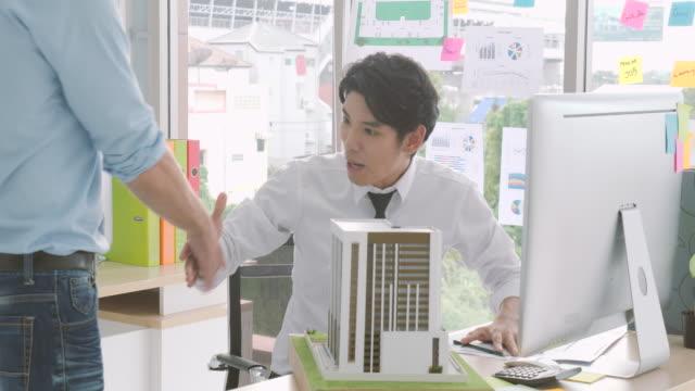 2 つのビジネス パートナーは、会うときに、手を振る。エンジニアはチーム作業です。男性建築家や同僚の建築モデルの構築 - ビジネスマン 日本人点の映像素材/bロール