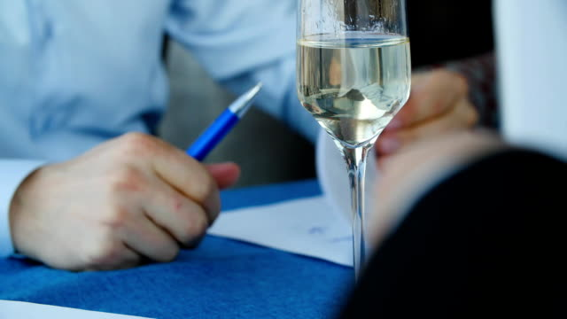 Two business partners signing document. Businessmen sign a contract at the restaurant, on the table is a glass of champagne video
