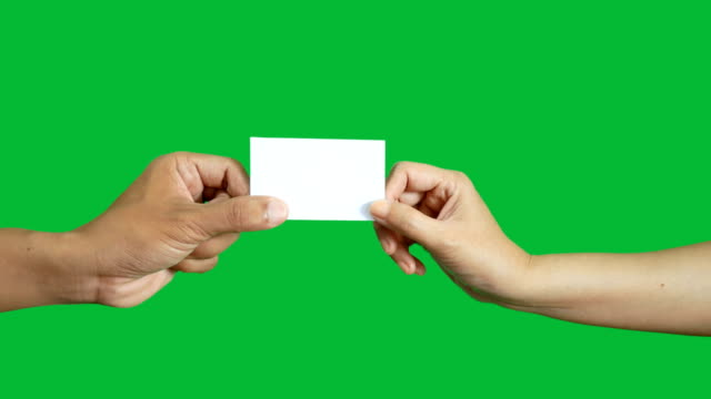 4K. two business people make business card exchange with each other's isolated on chroma key green screen background