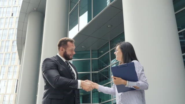 two business people man and woman shaking hands outdoors near business center - fiducia video stock e b–roll