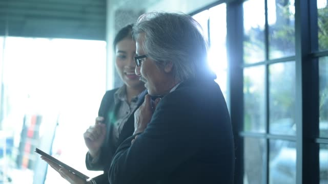 vídeos de stock e filmes b-roll de two business person are using tablet - senior business woman tablet