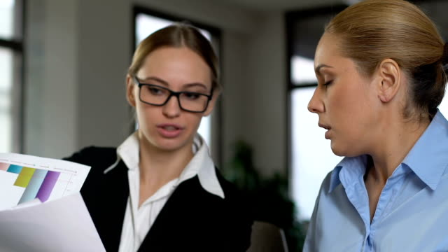 Two business women arguing in office, colleagues misunderstanding, work stress