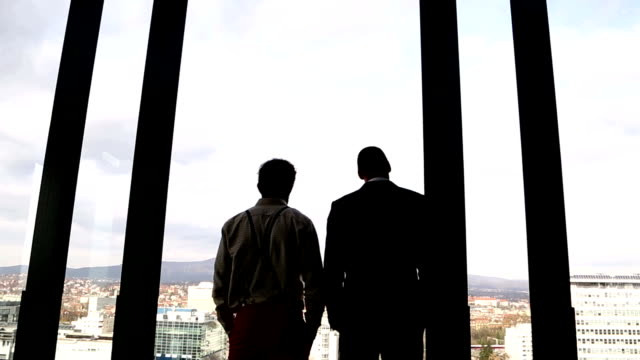 Two businessman looking on city through window video