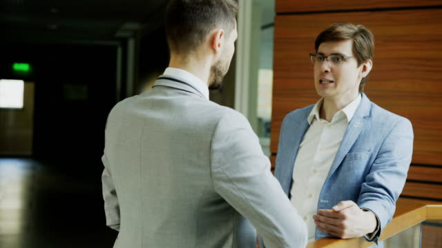 two businessman partners standing and chatting standing near railing in hall of modern business center - collega d'ufficio video stock e b–roll