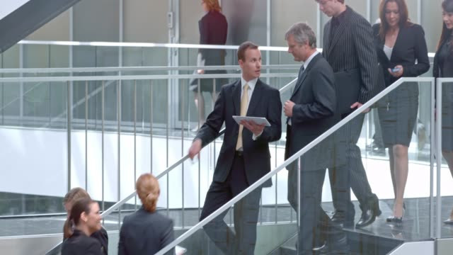 DS Two businessman talking over tablet on the stairs