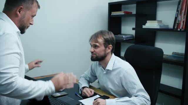vidéos et rushes de deux hommes d'affaires parlent dans le bureau, on regarde l'autre et montrant des signes sexuels - uniforme