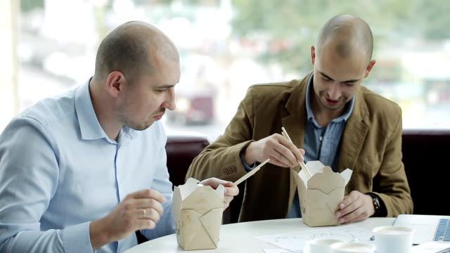 vídeos de stock, filmes e b-roll de dois empresários discutem o projeto durante o almoço. dois empresários comendo macarrão chinês e discutindo um projeto de negócios. - almoço