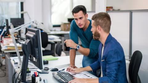 due uomini d'affari che discutono progetto in ufficio - due persone video stock e b–roll