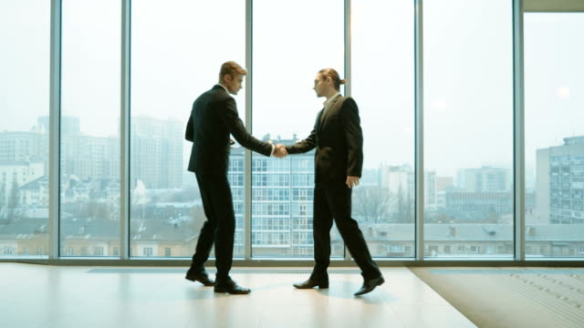 Two businessmen greeting each other on the background of a panoramic window. 4K